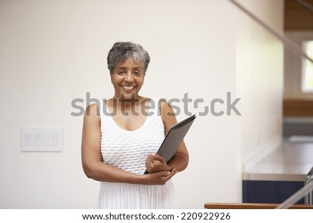 Senior African businesswoman holding paperwork - stock photo