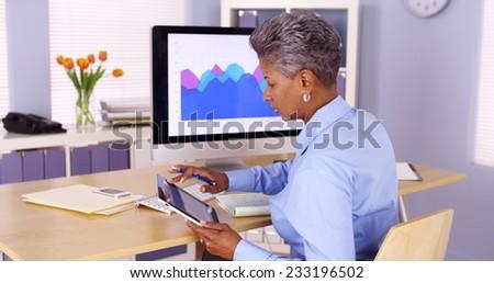 Senior African businesswoman multitasking at desk - stock photo