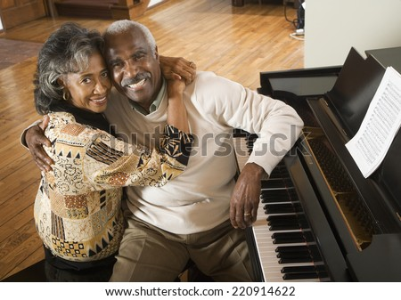 Senior African couple hugging next to piano - stock photo