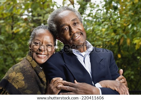 Senior African couple smiling in woods - stock photo