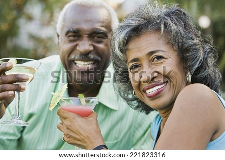 Senior African couple toasting with cocktails - stock photo