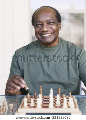Senior African man playing chess - stock photo