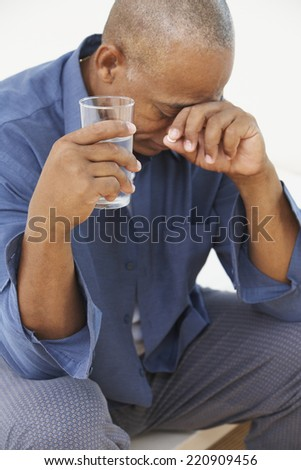 Senior African man with head in hand drinking glass of water - stock photo