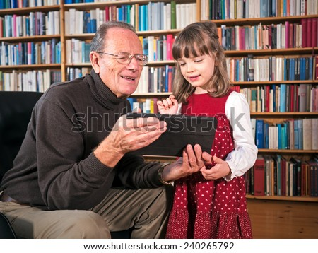 Senior and granddaughter looking at a tablet - stock photo