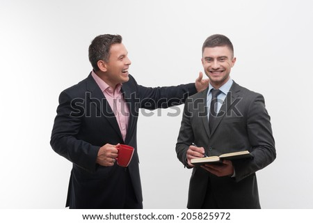 Senior and junior business people discuss something, boss with red cup patting shoulder of young employee, isolated on white background - stock photo