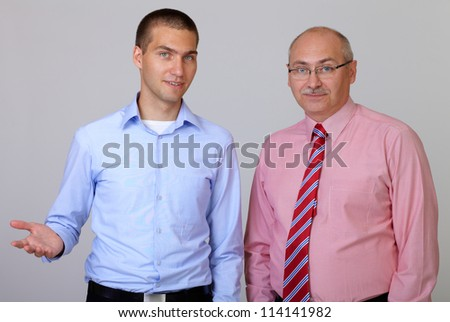 Senior and junior businessman discuss something during their meeting, isolated on grey - stock photo
