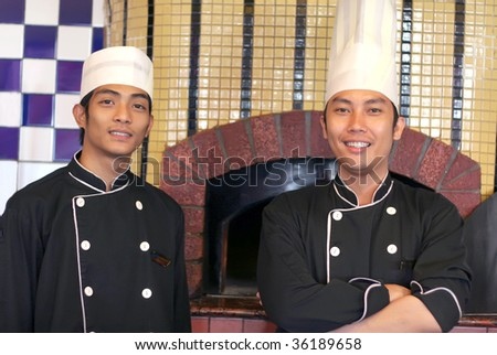 senior and junior chef pose at front of pizza oven - stock photo