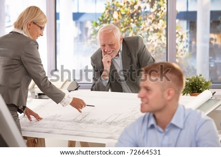 Senior and young architects working together in office, smiling.? - stock photo