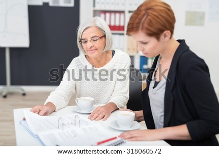 Senior and Young Businesswomen Reading Some Documents on the Table While Having Cups of Coffee. - stock photo