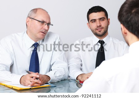 Senior and young colleague interview applicant for a job - stock photo