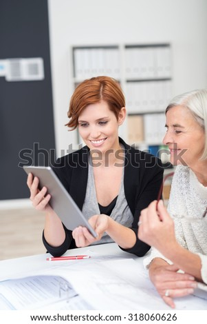 Senior and Young Happy Office Women Looking at the Tablet Screen Together at the Table inside the Workplace.