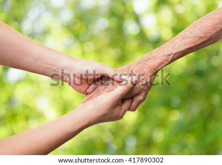 Senior and young holding hands on abstract nature background. - stock photo