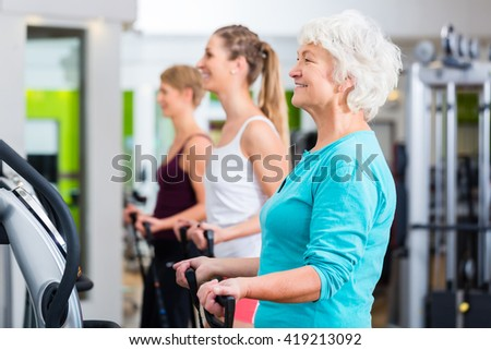 Senior and young people on vibrating plates in gym doing fitness exercise  - stock photo