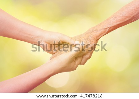 Senior and young women holding hands on abstract nature background and color tone effect. - stock photo
