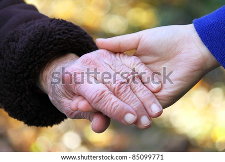 Senior and young women holding hands over shiny yellow leaves background - stock photo