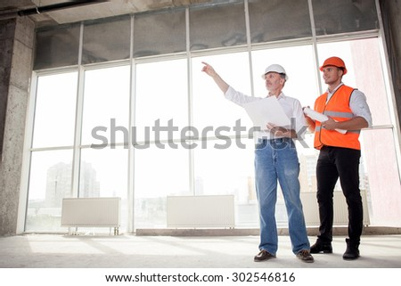 Senior architect and young builder are discussing new project. The architect is pointing his finger sideways seriously. The foreman is looking there with interest and smiling. Copy space in left side - stock photo