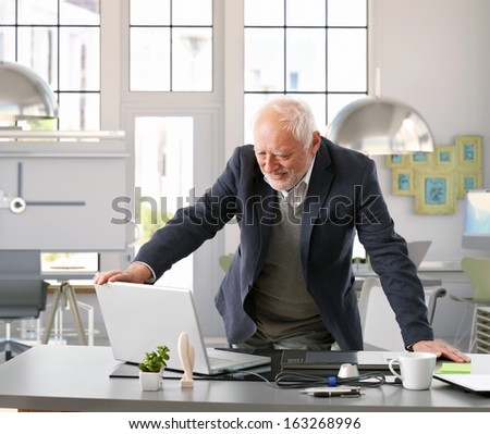 Senior architect standing by desk working with computer at office. - stock photo