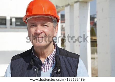 Senior architect standing in front of building, while using his mobile. Small business.