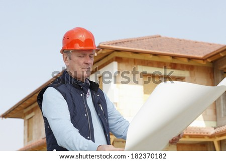 Senior architect standing in front of building with blueprint and hardhat. Small business.