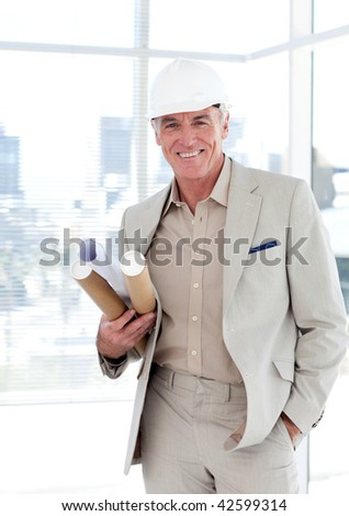 Senior architect with a hardhat holding blueprints in a building site - stock photo