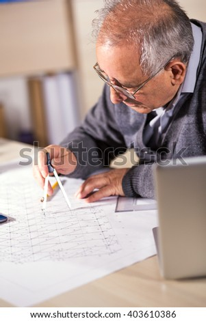 Senior architect working on construction blueprint in office, he draws with a divider.