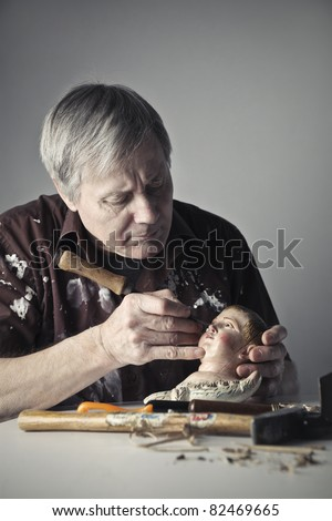 Senior artist restoring a wooden sculpture - stock photo