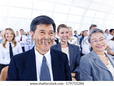 Senior Asian Businessman in Large Seminar - stock photo