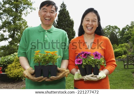Senior Asian couple holding potted plants
