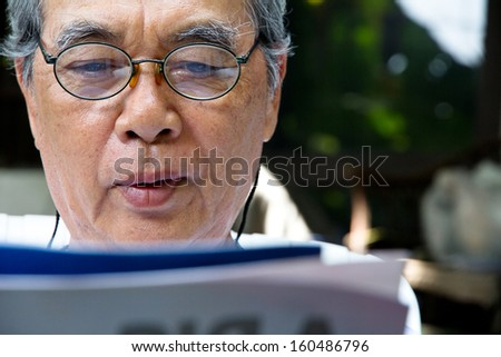 senior asian man enjoying at home reading a book - stock photo