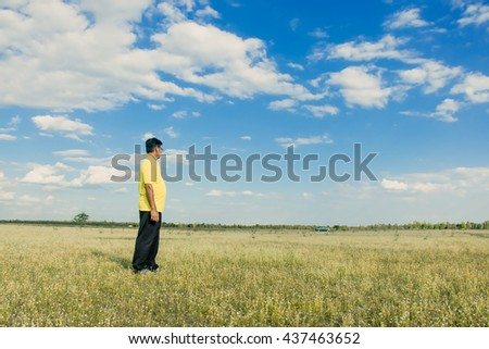 Senior asian man stand in the grass meadow look forward into the blue sky, family relax time and retired concept