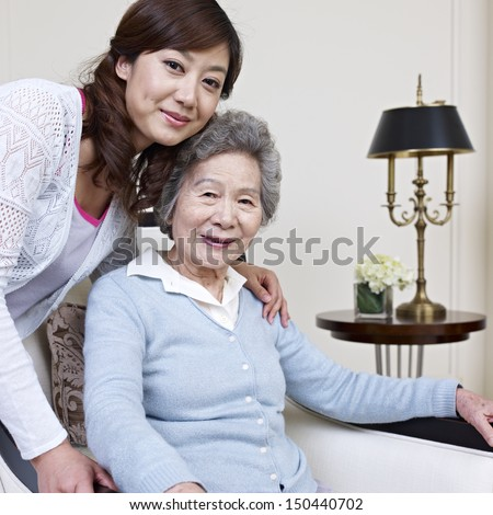 senior asian woman and her adult daughter. - stock photo