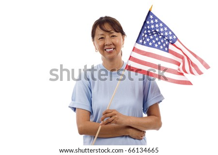 Senior Asian woman wearing a  blank blue shirt, holding an American flag isolated over white background - stock photo