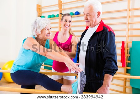 Senior at rehab in physical therapy having rehabilitation session - stock photo