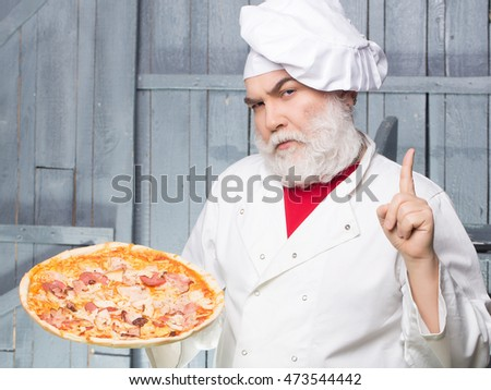 Senior bearded chef with pizza in white uniform with serious face and hat on wooden background