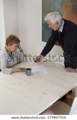 Senior broken down woman signing divorce documents - stock photo