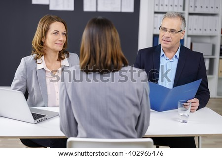 Senior business executive and his female colleague conducting an interview with a young woman job seeker, over the shoulder focus to his face - stock photo