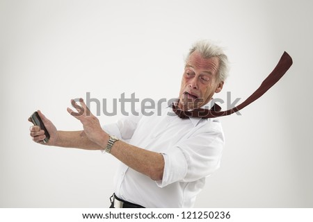 Senior business executive in the teeth of a hurricane being blown backwards by the wind raising his hands defensively , conceptual of helplessness in the face of a business disaster - stock photo