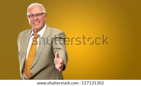 Senior Business Man Offering Handshake Isolated On Coloured Background - stock photo