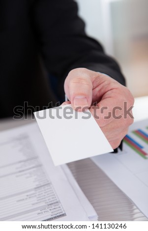Senior Business Man Offering Visiting Card At Desk In Office