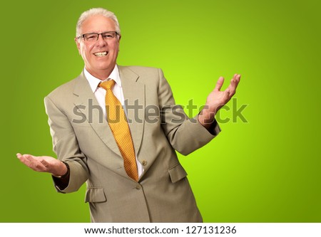 Senior Business Man Presenting Isolated On Green Background - stock photo