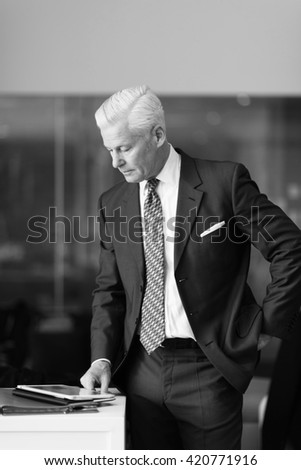 senior business man reading reports on tablet computer at modern office interior - stock photo