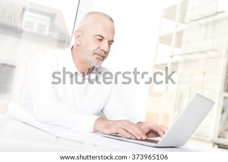 Senior business man sitting in front of laptop in bright modern office   - stock photo