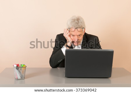 Senior business man thinking with laptop