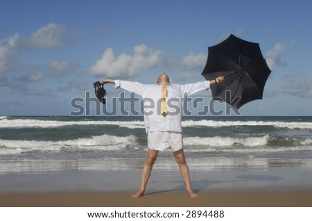 Senior business man undressed with arms outstretched on a tropical caribbean beach.  Retirement freedom concept.