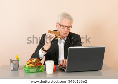 Senior business man with laptop eating his bread meal at the office