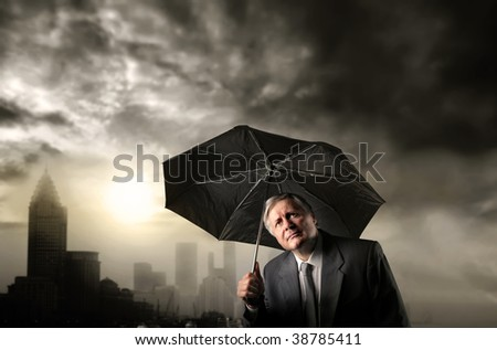 senior business man with umbrella and a stormy weather