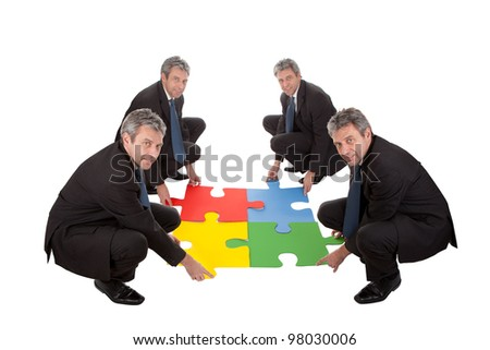 Senior business people assembling a jigsaw puzzle. Teamwork concept. Isolated in white