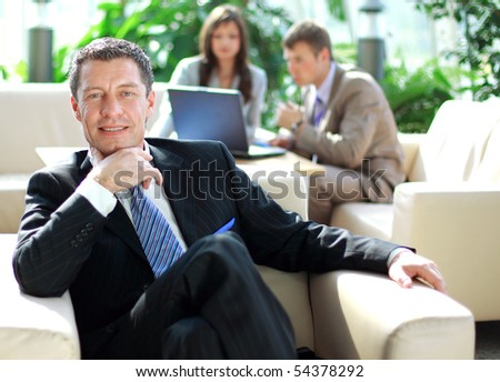 Senior business relaxed on a chair with his colleagues at a meeting in the back - stock photo