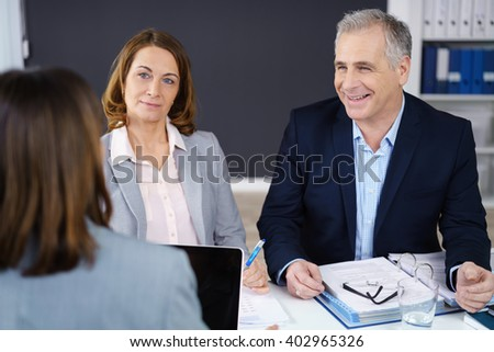 Senior business team in a management meeting sitting having a discussion around a table in the office, focus to a smiling businessman - stock photo