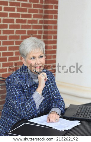 Senior Business Woman Happy and Confident Mature Elderly Senior Citizen Holding a Pen While Thinking and Looking to the Side While Sitting at a Desk - stock photo